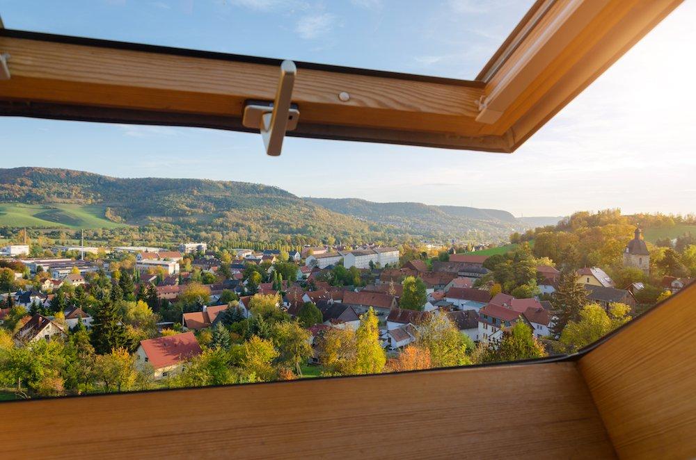 Aussicht aus einem Dachfenster über ein ländliches Wohngebiet.