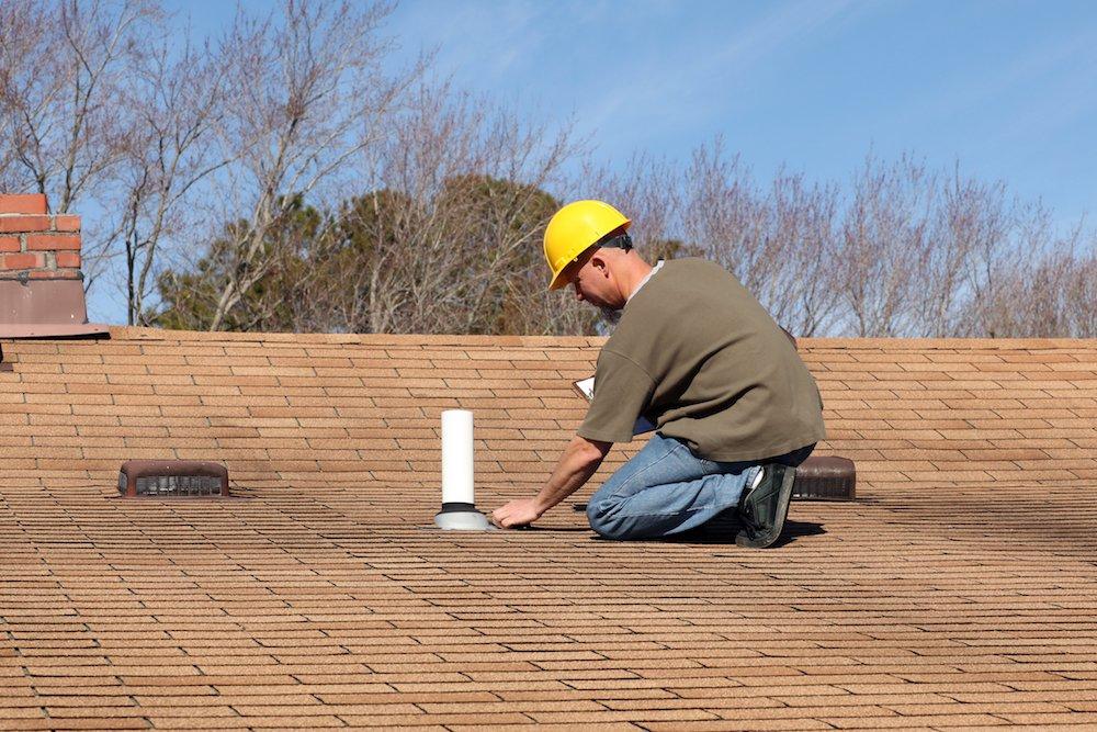 Dachdecker bei der Inspektion eines Steildaches