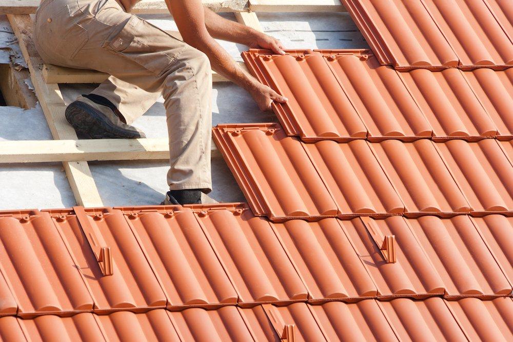 Ein Steildach wird mit Dachpfannen gedeckt