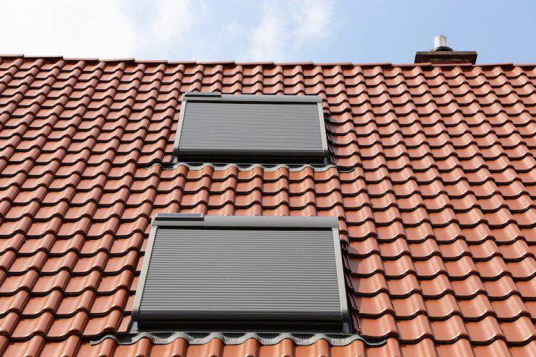 Zwei Dachfenster mit Sonnenschutz auf einem Steildach.