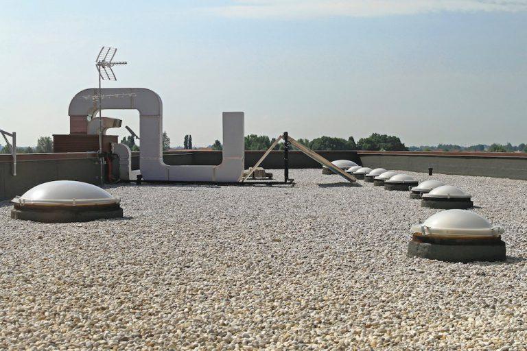 Flachdach mit Lichtkuppeln und einer Auflast aus Kies