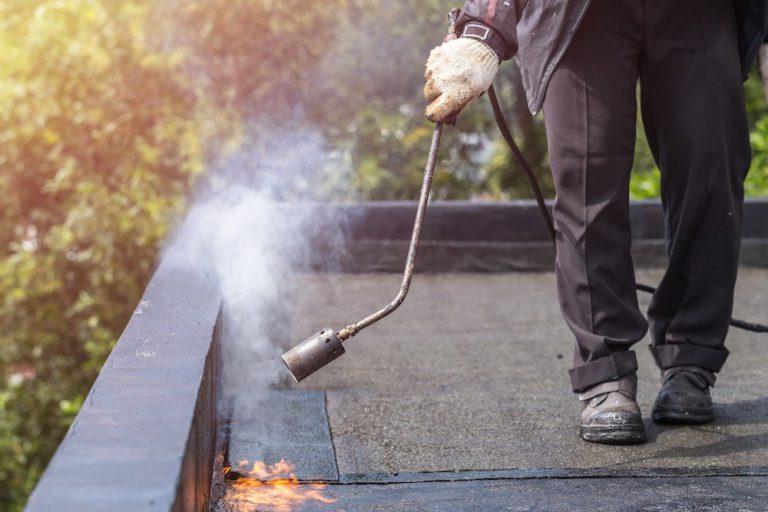 Eine neue Bitumenbahn wird auf einem Flachdach verschweißt.