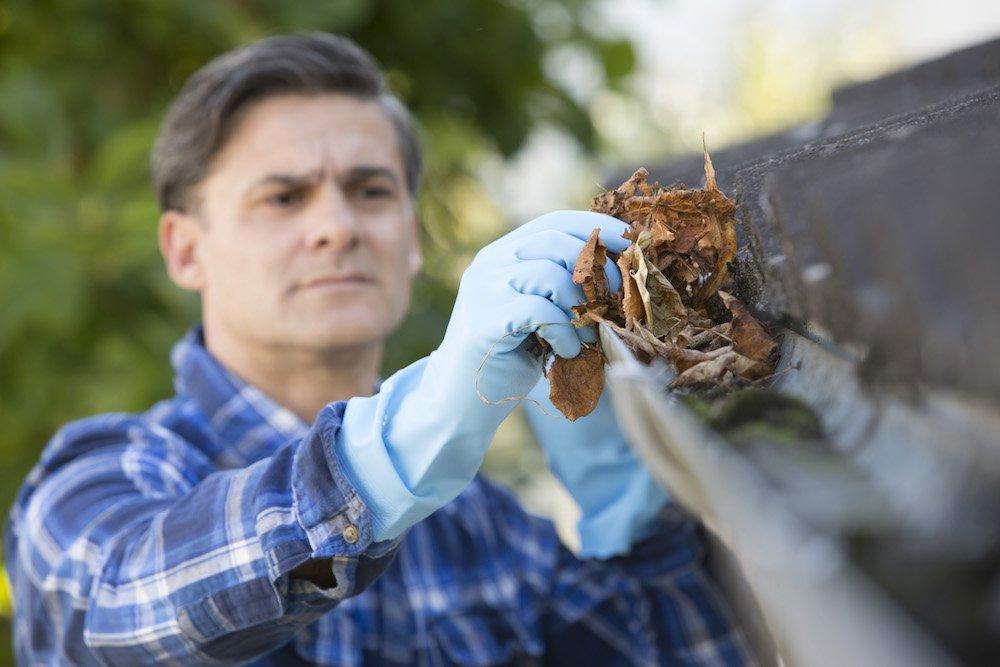 Mann reinigt Dachrinne per Hand